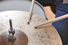 Close Up On Man Holding Drumsticks Drumming On Cymbal