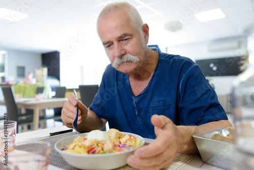 Fotografija senior man eating lunch in restaurant