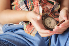 Midsection Of Child Holding Pocket Watch