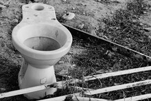 Abandoned Toilet Bowl On Field By Rusty Metallic Railing