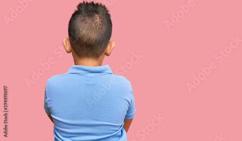 Fotografía Little boy hispanic kid wearing casual clothes standing backwards looking away w