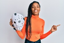 African American Woman Holding Hockey Mask Smiling Happy Pointing With Hand And Finger To The Side