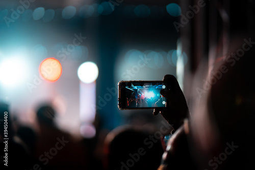 Fotografija Person close up of recording video with smartphone during a concert
