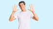 Leinwandbild Motiv Young handsome man wearing casual white tshirt showing and pointing up with fingers number ten while smiling confident and happy.