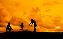 Silhouette Parents Playing With Son On Mountain Against Orange Cloudy Sky During Sunset
