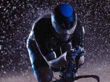 Triathlon Athlete Riding Bike On Rainy Night