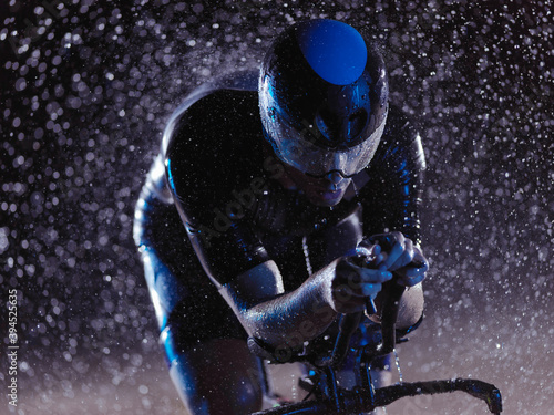 Slika na platnu triathlon athlete riding bike on rainy night
