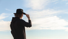 Young Man Looking To The Side In A Black Hat. Blue Sky Background With White Clouds. Relaxation, Leisure And Free Time Concept.