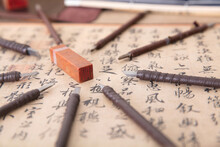 A Large Number Of Carving Knives Surround A Stone Seal On Chinese Calligraphy Works
