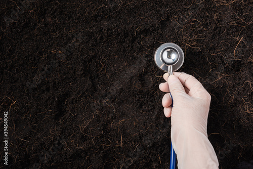 Fototapeta Hand of researcher woman wear gloves holding a stethoscope on fertile black soil for check condition before agriculture or planting, Concept of World Soil Day, Earth day and hands ecology environments obraz