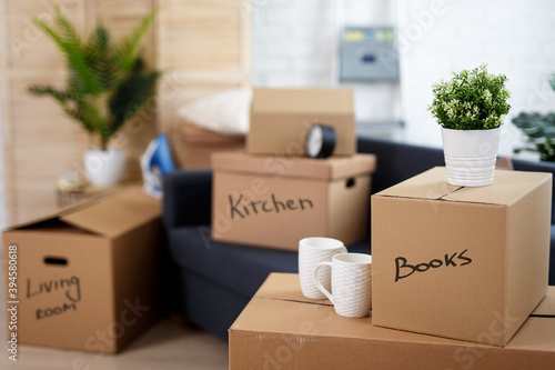 Fototapeta moving day - close up of cardboard boxes with belongings stacked in new house