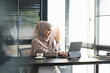 A happy muslim businesswoman in hijab is working on computer tablet at her office room.