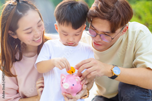Obraz na plátně happy parent help son putting a coin into  piggy bank