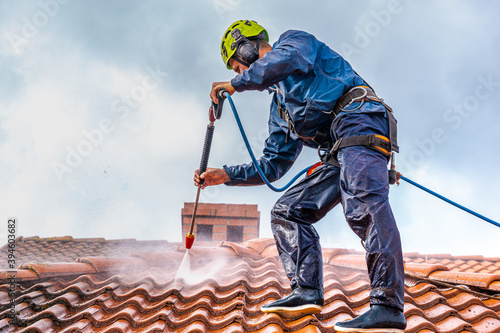 worker washing the roof with pressurized water #394603682