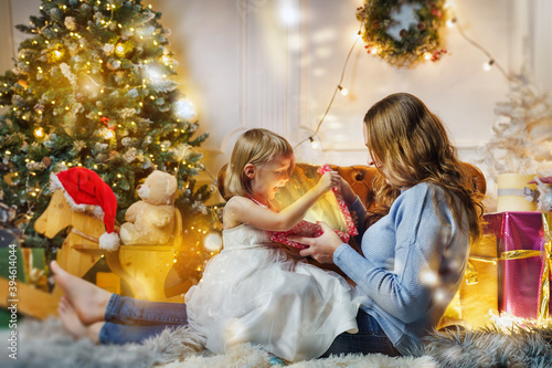 Fototapeta Mother and daughter at christmas eve in bright decorations