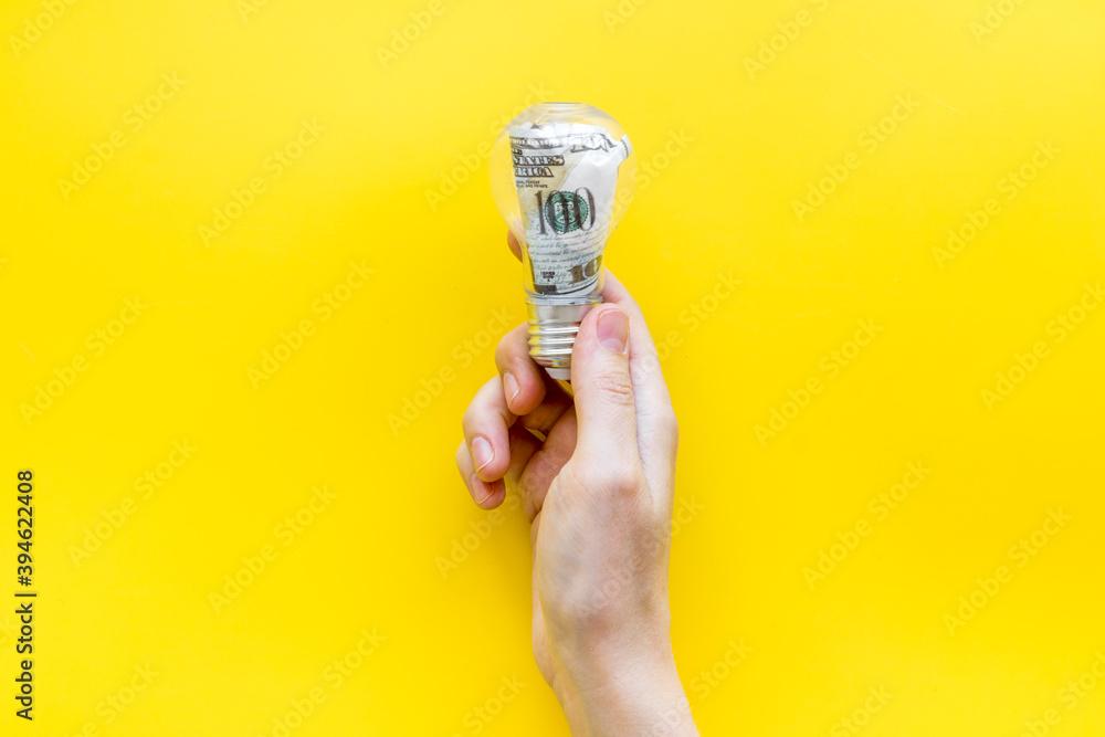 Fototapeta Money making idea concept with light bulb and dollar inside