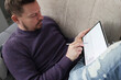 Man lies on couch and works on tablet. Remote work from anywhere in the world concept
