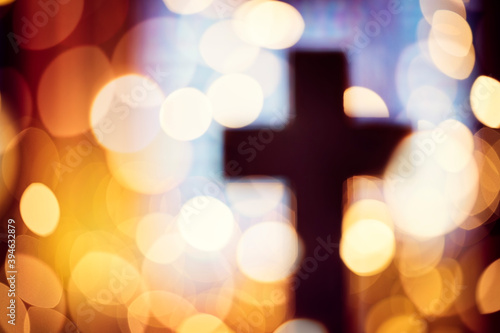Photographie Abstract cross silhouette in church interior against stained glass window concep