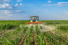 Tractor In The Field Applies Fertilizer To The Soil