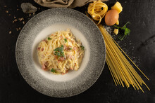 Spaghetti With Cheese And Bacon. A Plate Of Hot Pasta, Egg, Cheese And Herbs On A Black Stone Kitchen Table.