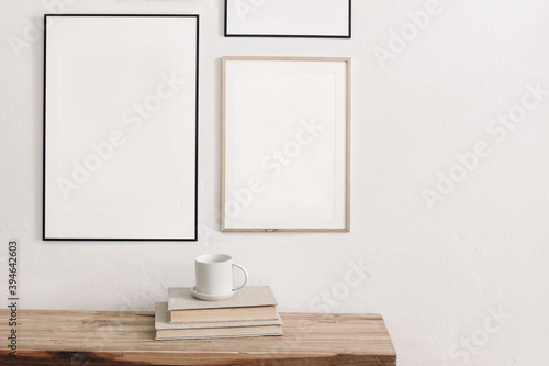 Fototapeta Set of black portrait picture frame mockups. Wall art gallery. Cup of coffee on pile of books on old wooden bench, table. White wall background. Scandinavian interior, neutral color palette. obraz