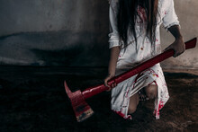 Midsection Of Evil Woman Holding Knife Covered With Blood Against Wall