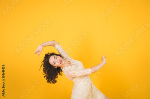 Graceful classic ballerina dancing on yellow studio Canvas Print