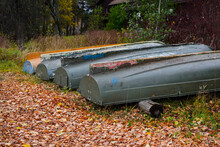 Boat Station On The Lake In The Village. Old And Rusty Boats Are Pulled Ashore And Turned Upside Down For Winter Storage. Many Fallen Leaves Around