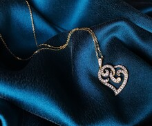 Close-up Of Heart Shape Pendant With Chain On Blue Fabric