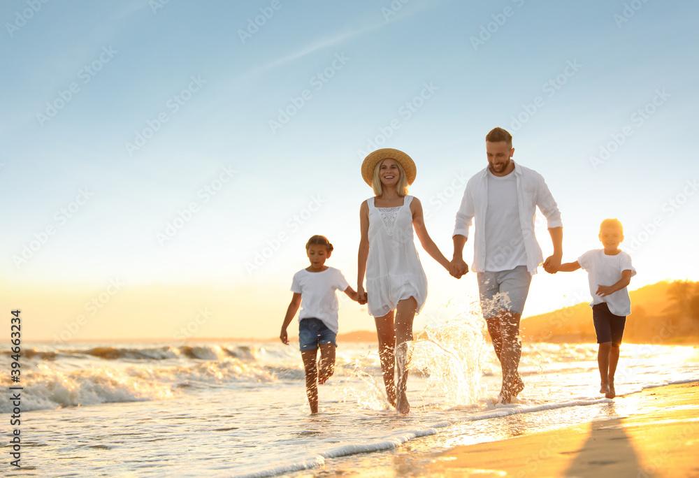 Fototapeta Happy family on sandy beach near sea at sunset