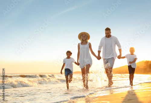 Happy family on sandy beach near sea at sunset Fototapeta