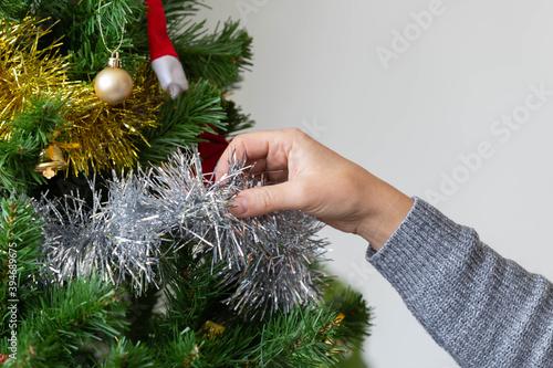 Fototapeta Closeup of woman hand decorate the Christmas tree for Christmas pary obraz