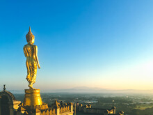 Golden Buddha Statue On Wat Phra That Khao Noi View Point, Nan, Thailand, Famous Landmark Of Golden Buddha Image On The Top Of Mountain With Morning Blue Sky Background