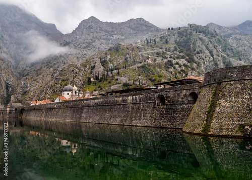 Fototapeta The well preserved city walls, which date back to the 17th and 17th centuries. The day is cloudy and there is fog. Kotor, Montenegro. obraz na płótnie