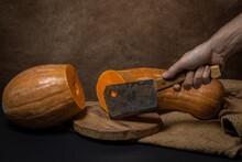 The Hand Cuts The Pumpkin In Half With An Ax. Long Pumpkin. Autumn Vegetable.