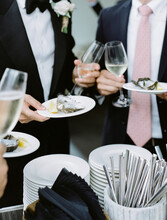 Two Men In Suits Holding Glasses Of Wine And Plates Of Oysters At A Wedding