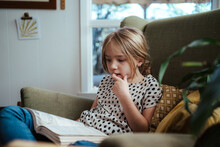 Young Girl Reading A Book At Home