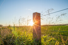 Setting Sun Shines From Behind Rural Paddock Fence Post