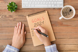 Fototapeta Kawa jest smaczna - Woman making to-do list on 2021 year at table