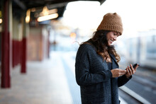 Asian Woman Waiting At Train Station Using Mobile Phone
