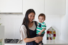 Happy Mother Holding Baby Boy In Kitchen