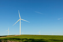 Wind Turbines Against Blue Sky And Green Farmland