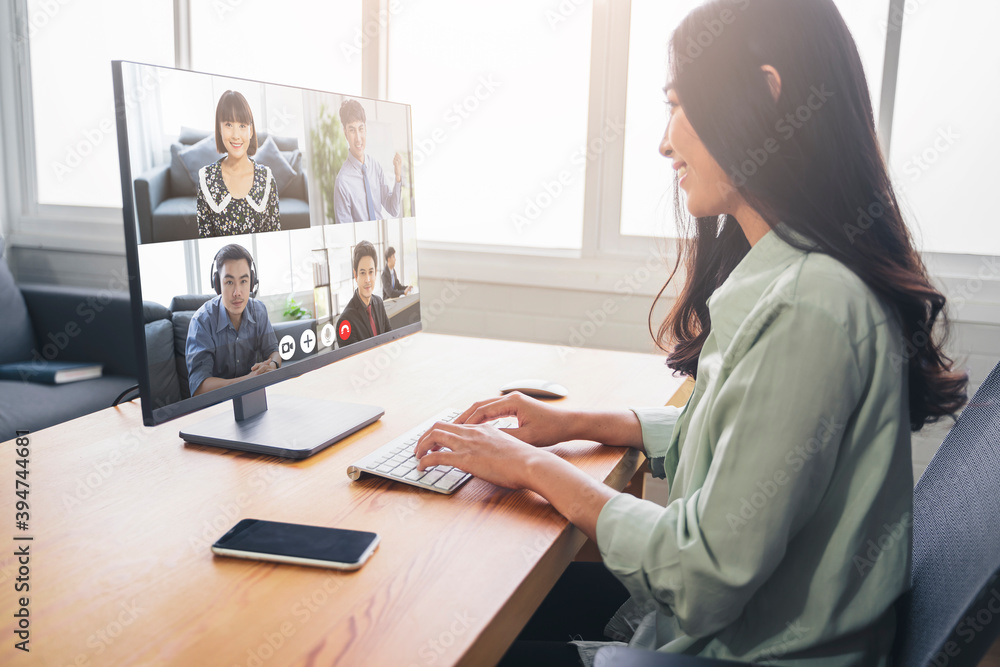 Fototapeta Beautiful Asian business woman in business conference meeting online video call network connection work from home, planning talking strategies using laptop technology, thinking smiling, modern office