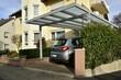 canvas print picture - Neuer grauer Carport aus beschichtetem Aluminium mit Pult-Glasdach an einem Wohnhaus