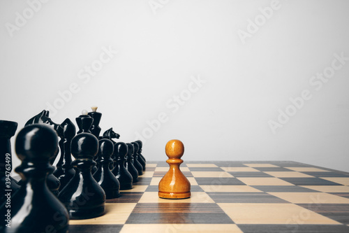 Chessboard with wooden figures against grey background Fotobehang
