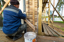 Worker In Protective Gloves Is Painting By The Brush The Facade House That Is Under Construction, Remodeling, Renovation, Extension, Restoration And Reconstruction. Concept Of Home Improvement Or