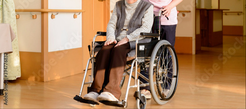 Fényképezés 老人福祉施設 高齢者が座る車イスを押す介護スタッフ