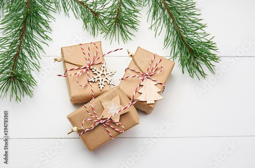Christmas gift boxes with pine tree branches on white wooden background Fototapet