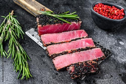 Fototapeta Rare Ahi tuna steak slices on a meat cleaver. Black background. Top view obraz