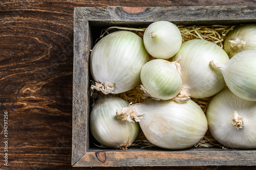 Fotografiet White raw onion in wooden box. Wooden background. Top view